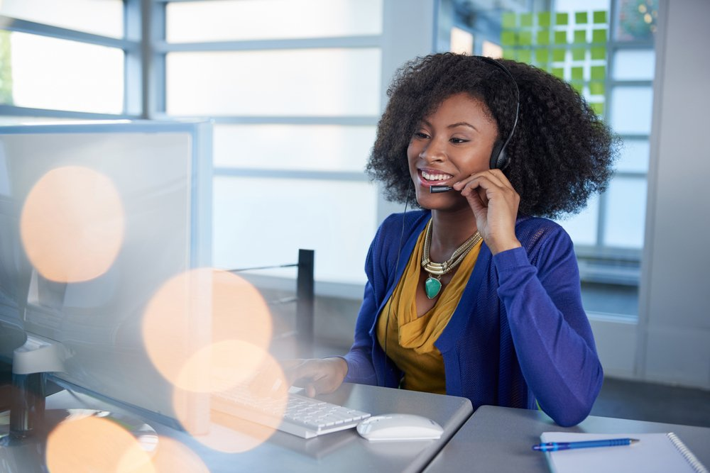 Portrait of a smiling customer service representative with an afro at the computer using headset