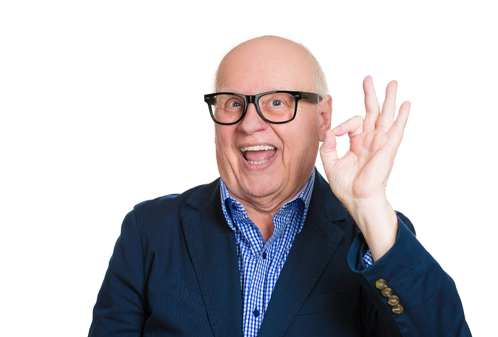 Closeup portrait, happy, cheerful, smiling, senior mature nerd man in black glasses, showing OK sign, isolated white background. Positive human emotions, facial expressions, feelings, attitude